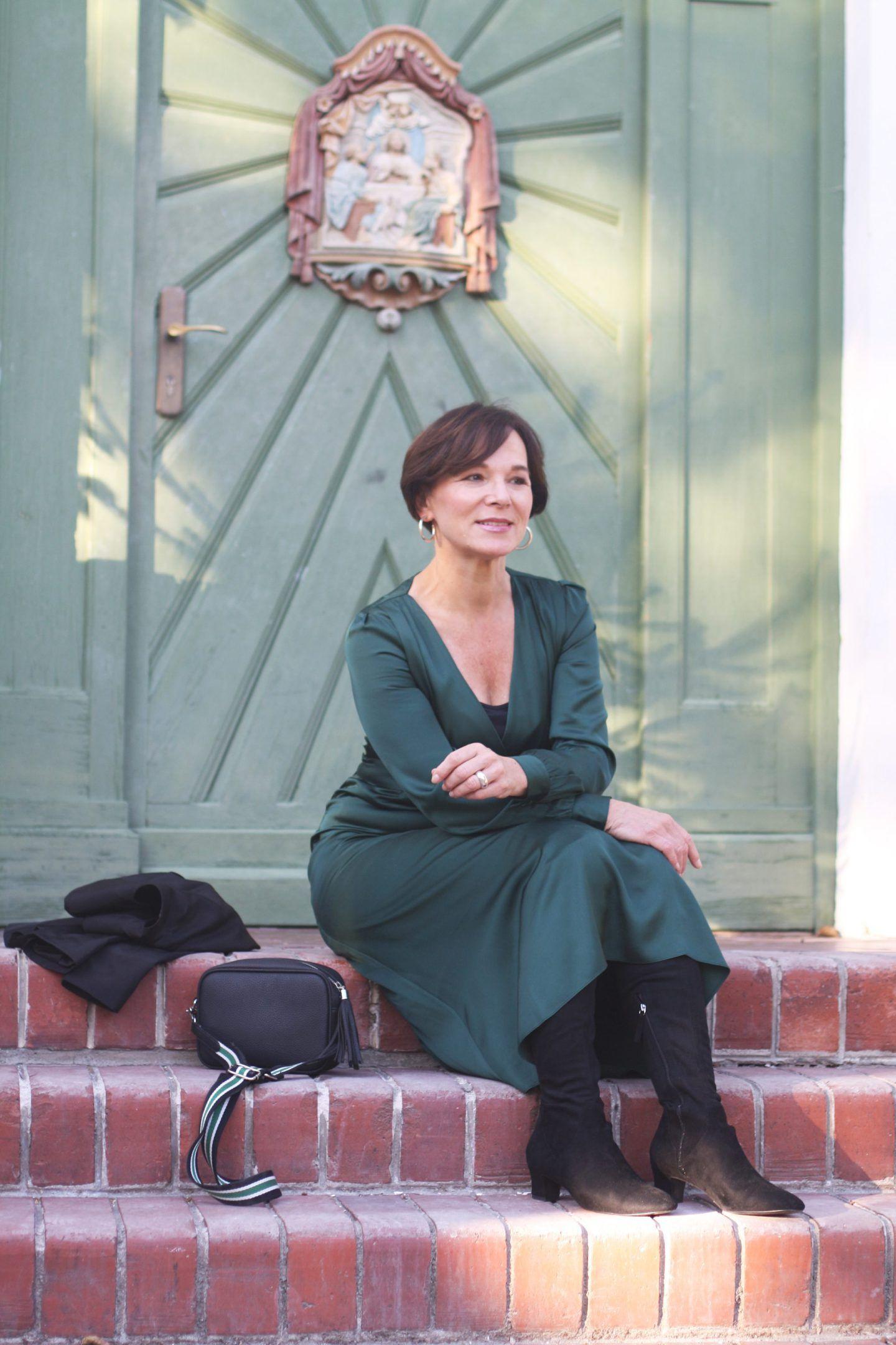 femininer look in grünem kleid und schwarzem blazer