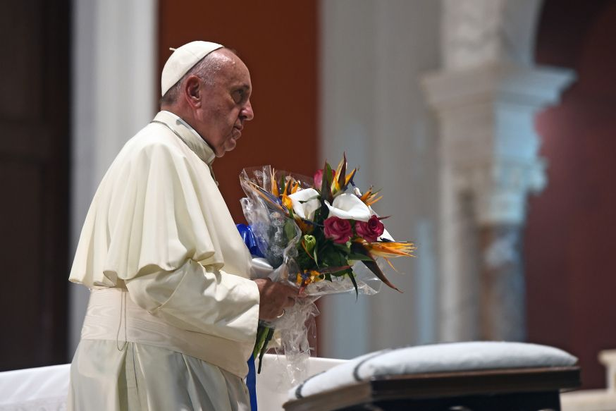 Pope Francis holds flowers at the basilica of Our Lady of Charity of El Cobre -patron saint of Cuba- in El Cobre, Santiago de Cuba on September 21, 2015. Santiago, the last stop on Pope Francis's Cuban tour, is known for its revolutionary history, its rum and the troubadours who have infused the Caribbean island's music with their tropical beats.  AFP PHOTO / FILIPPO MONTEFORTE
