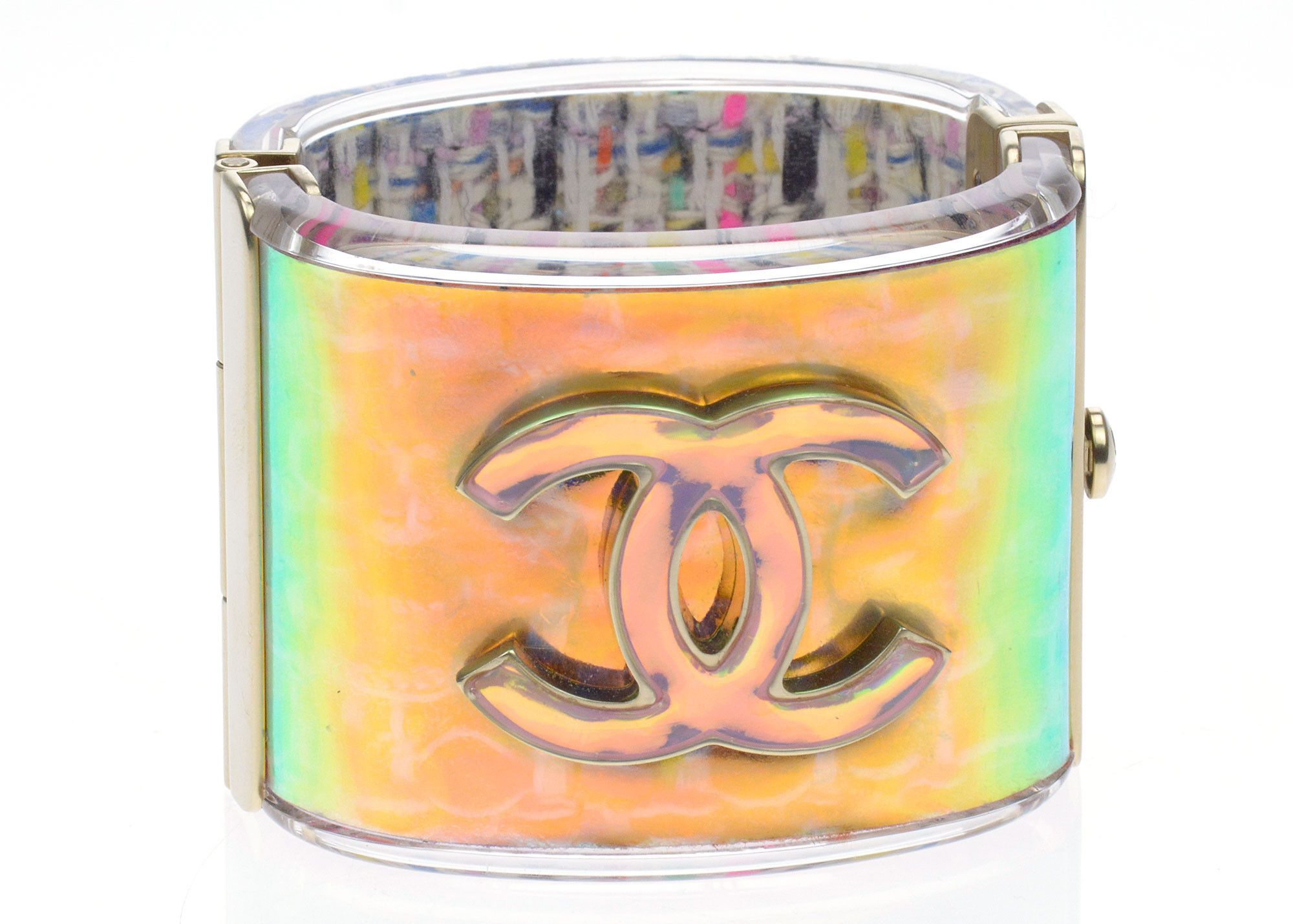 Chanel Multicolor Hologram Cuff is absolutely stunning! Featured in iridescent acrylic, this hologram cuff features an interlocking CC logo on the front and classic tweed printed on the interior. This