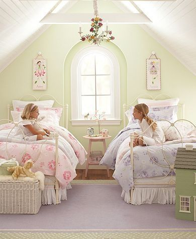 I like these matching white bed frames. Add the sheer princess textiles over both beds. Add pink night stand in the middle.