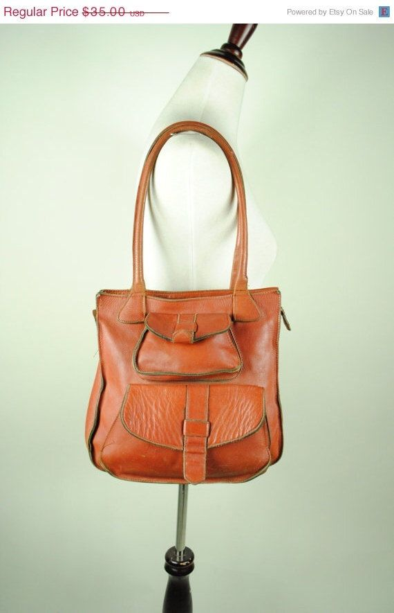Awesome brown leather bag. It features two front flap pockets  and one open pocket on the back, zipper closure for main compartment.  No lining.