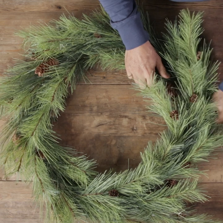Store-bought wreaths are gorgeous, but everyone knows that they can be costly. This DIY wreath hack uses cardboard to craft a sturdy, inexpensive wreath base. Our simple evergreen wreath features natural elements from both fall and winter for a transitional wreath that you can keep up November through January. #diywreath #wreathhack #easychristmaswreath #cheap #budget #bhg