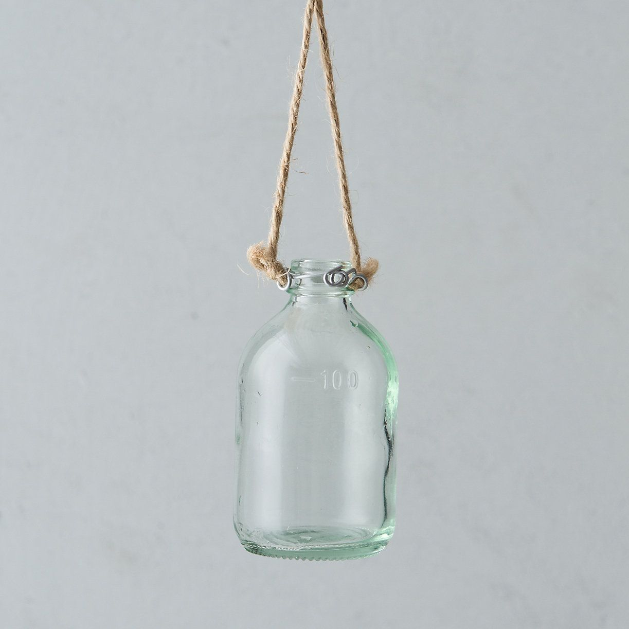 "Hanging Bud Vase Choose your favorite fresh cuts and suspend a cluster of these petite, bottle-shaped vases from garden branches or around the house for a blooming statement.  - Glass, jute twine - Wipe clean with damp cloth - Indoor or outdoor use - Hanging rope: 13""L - Imported  3.75""H, 2""diameter"
