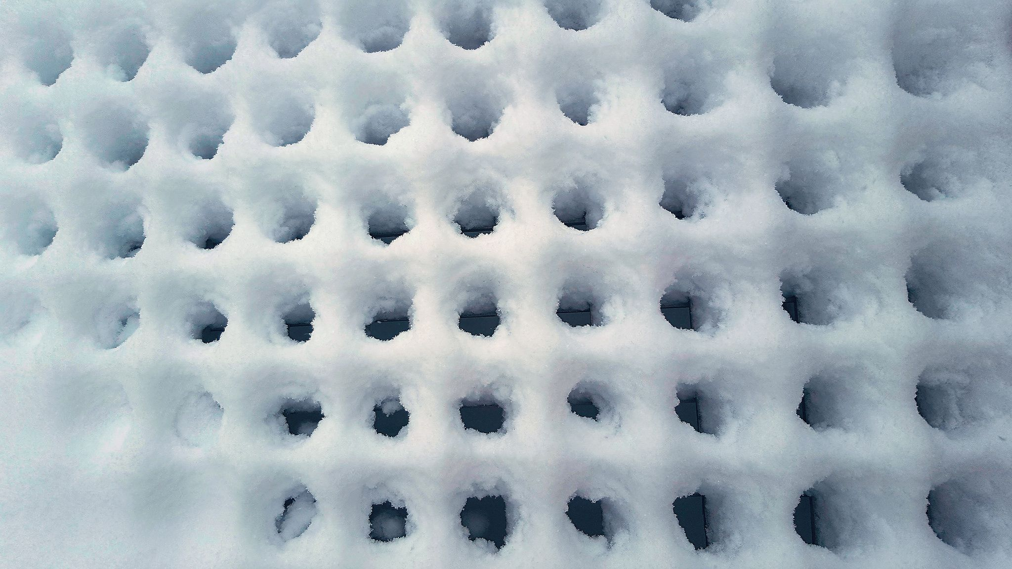 Winter Texture VI: A week of abstract textures inspired by the frigid beauty of Canadian winter. Today, fresh snow piles thickly over a fallen lattice fence, creating a softly waffled pattern in the snowbank.
