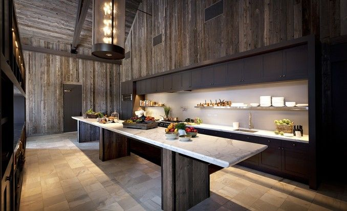 A modern kitchen integrated into the wall contrasts nicely with the  reclaimed wood walls.