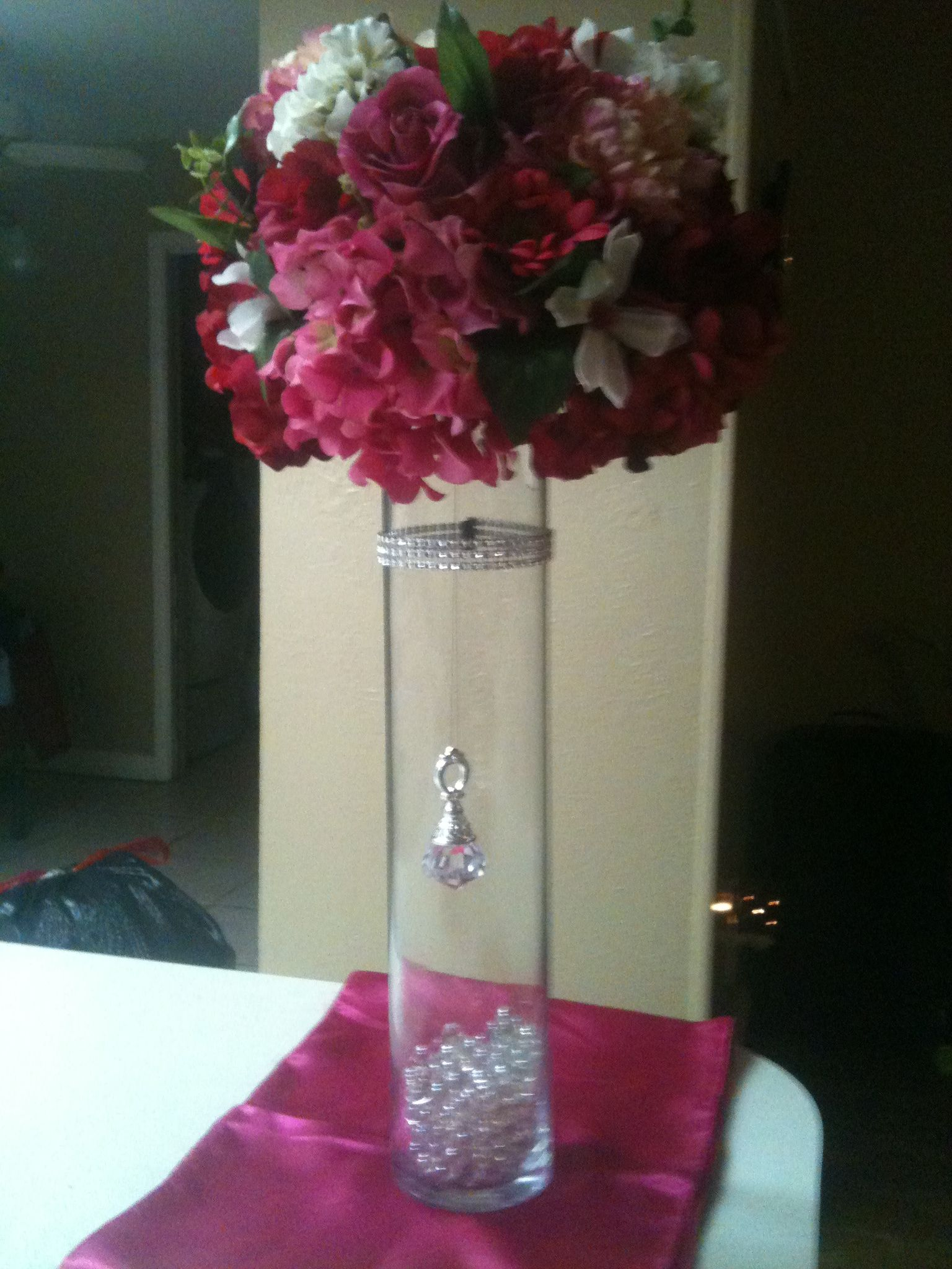 Hot pink roses, hydrangeas and other white flowers with a crystal (rhinestone) band and hanging crystal. May use colored water (pink?)