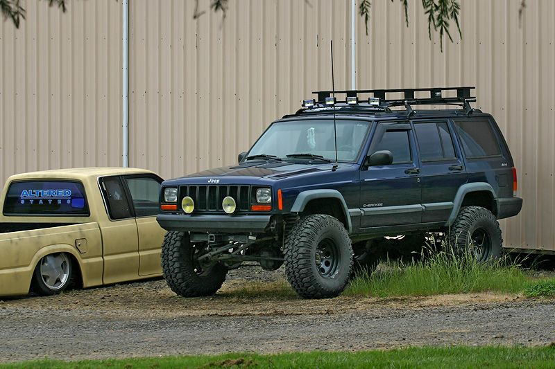 Lifted Xj With Roof Rack In Front Of Surco Rack Mounted On Yakima Cross Bars And Gutter Mounts Jeep Xj Jeep Cherokee Xj Jeep Life