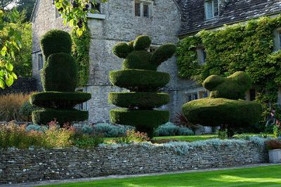 THROUGHAM COURT, GLOUCESTERSHIRE. DESIGNER: CHRISTINE FACER: THE OLD TOPIARY GARDEN WITH THROUGHAM COURT BEHIND
