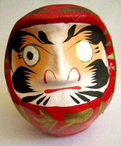 daruma doll /だるま人形/ only has one eye painted in, so as to remind you of the thing you have yet to complete. Once the achievement is reached, you can paint in the other eye.