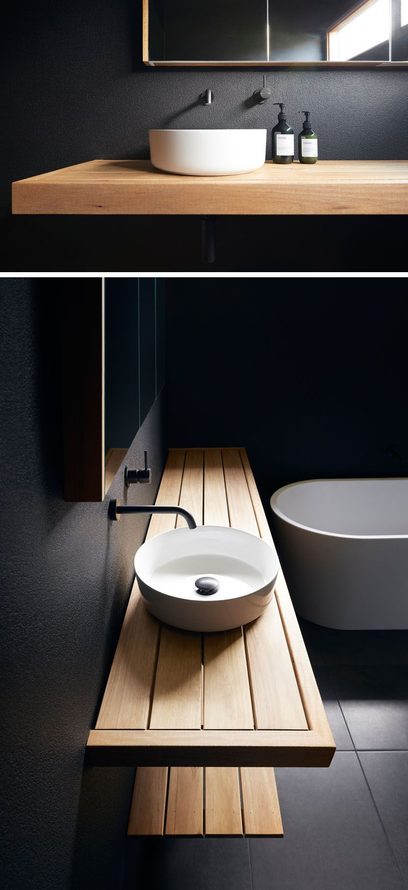 Photo of This modern bathroom has matte black walls, a wood vanity, and a white basin and…