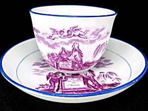 """Circa: 1817  Size: 5.5"""" - 13.8cm  Manufacturer: No makers marks.    1817 PRINCESS CHARLOTTE IN MEMORIAM PORCELAIN CUP AND SAUCER WITH BLUE TRIM. Grieving figures and putti carrying a crown. The popular princess was the only child of The Prince of Wales (Later King George IV) and died in childbirth changing the line of succession. 235."""