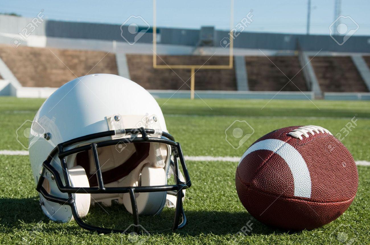 Fútbol americano y el casco en campo con el objetivo puesto en ... 623ab904291