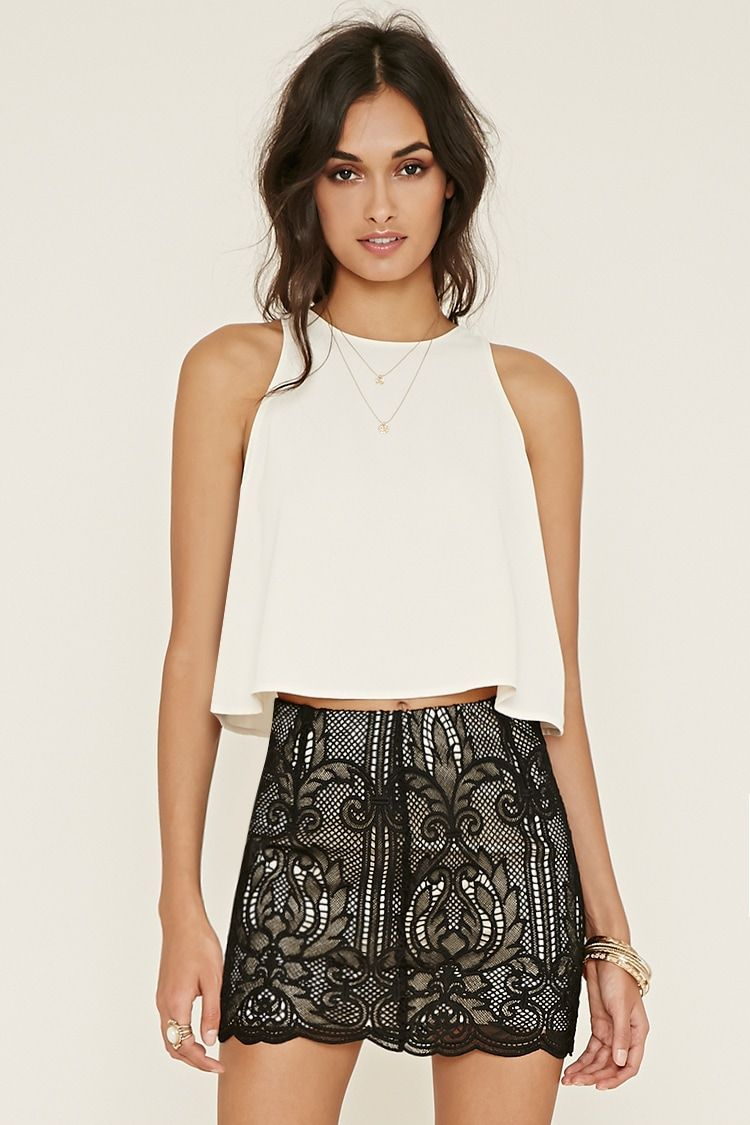 This mini skirt is complete with an ornate embroidered crochet overlay, a scalloped hem, and a concealed side zipper.