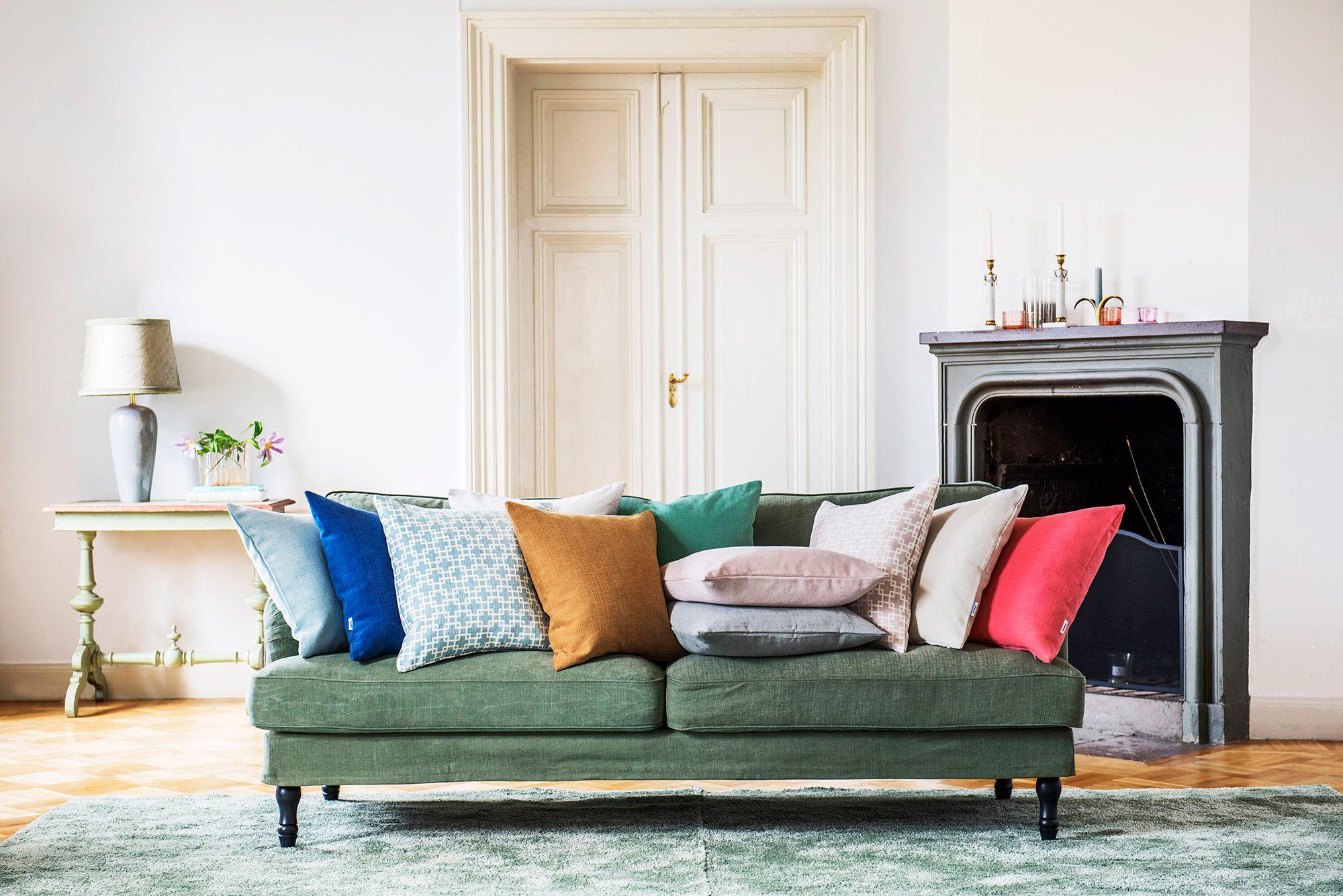 An eclectic mix scatter cushions en masse Green sofa