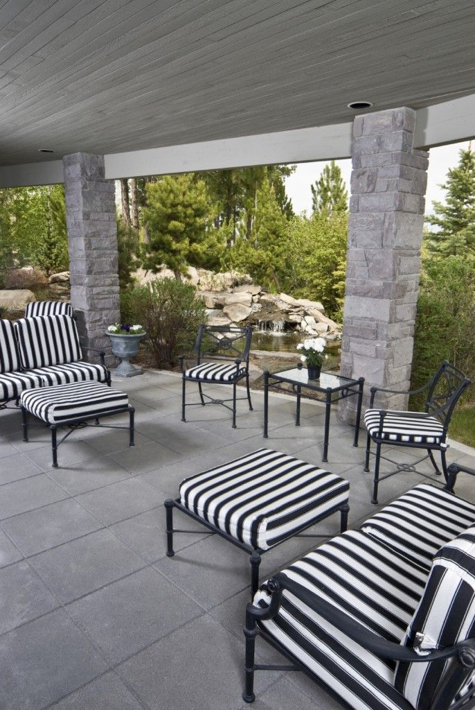 Mesmerizing Black And White Striped Patio Furniture Provides A Striking Contrast To The Light Gray Stone Tile Columns Of This Covered
