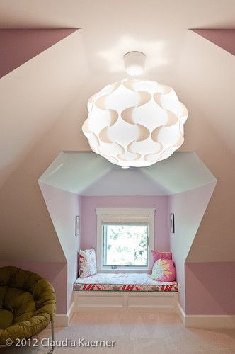 This cozy reading nook is the focal point of a front dormer. The banquette has pullout drawers below.
