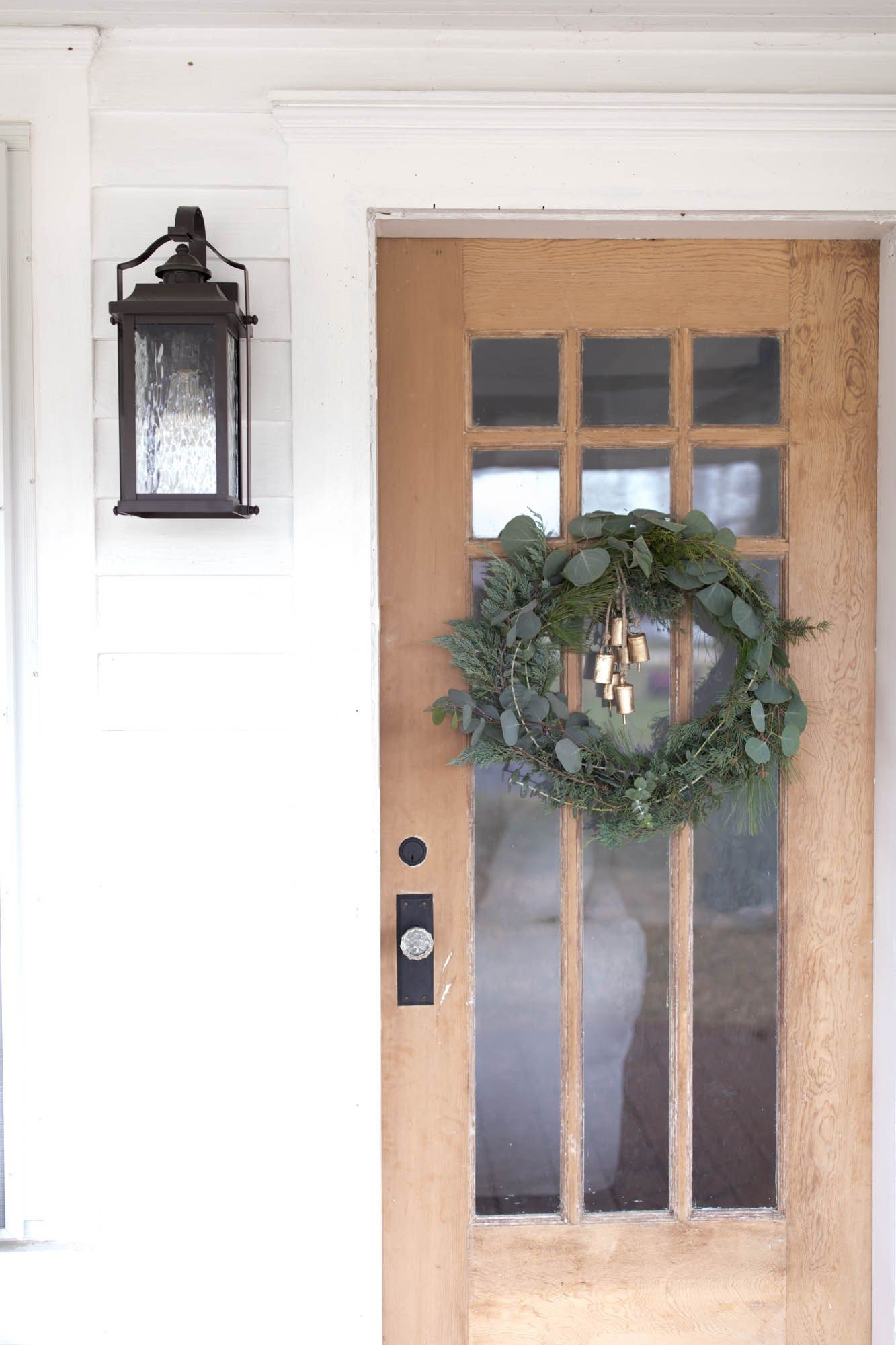 farmhouse christmas front porch decor neutral colors natural elements fresh greenery and red grain sack create a cozy space for the holiday season - Christmas Front Porch Decorations Pinterest