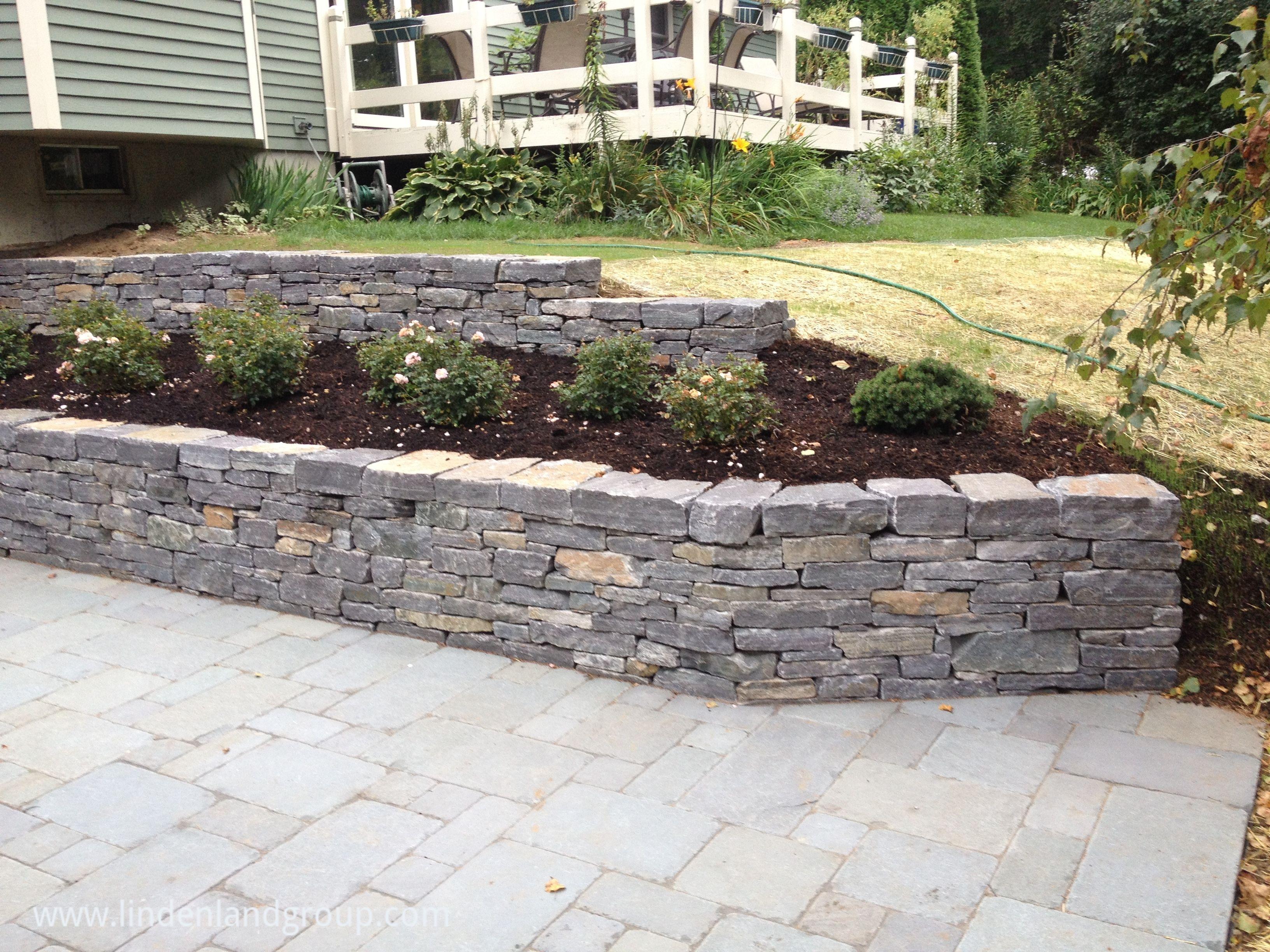American Granite Retaining Walls And Tumbled Bluestone Patio In Shelburne Vermont Diy Patio Patio Stones Concrete Patio Makeover