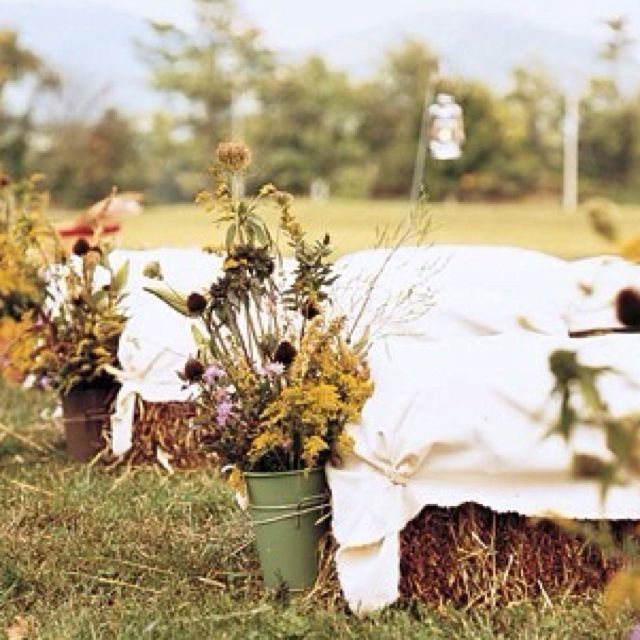 Hay bale seating at a wedding....pretty sap buckets with flowers ...
