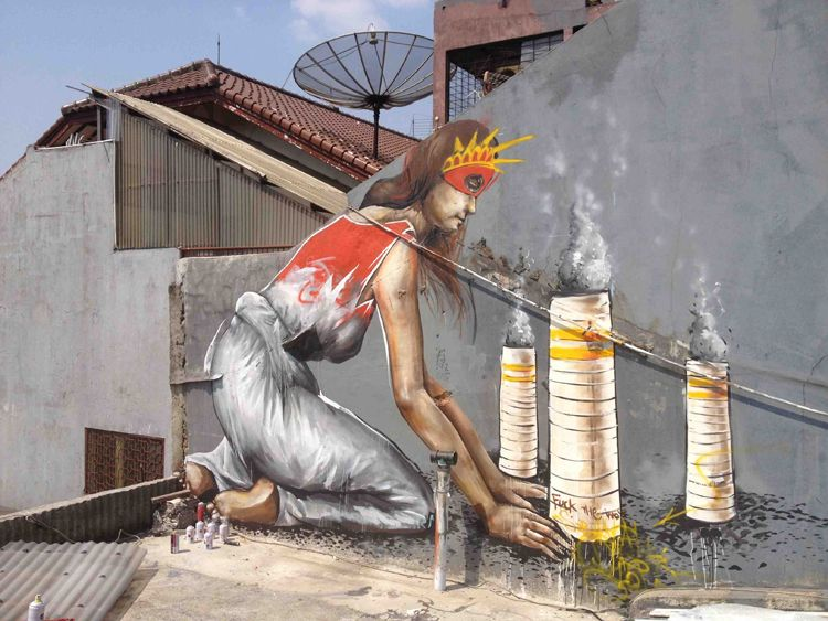 """Fintan Magee was recently in Jakarta, Indonesia for a residency with ISAD Studios and produced this bit of commentary. The mural shows a masked Lady Liberty building smoke stacks as if they were sand castles, with pollution coming from them and one of the towers scrawled with the words """"Fuck the world"""" on it. The figure is symbolic of America and it's childlike naivete of how its toys are affecting the rest of the world. #fintanmagee http://www.widewalls.ch/artist/fintan-magee/"""