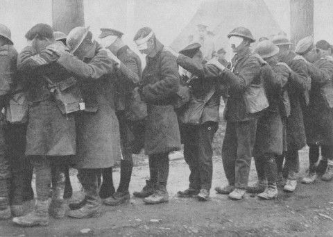 """FORETASTE OF THE FUTURE    Of all the forms of gas used in the Great War, that which had the least disastrous consequences was """"tear gas."""" Its effect was to inflict temporary blindness on those who came in contact with it. This pathetic row of figures show men temporarily blinded in that way on the Western Front in April, 1918. Affecting as this scene is, the results of the deadly gases of today would be infinitely worse."""