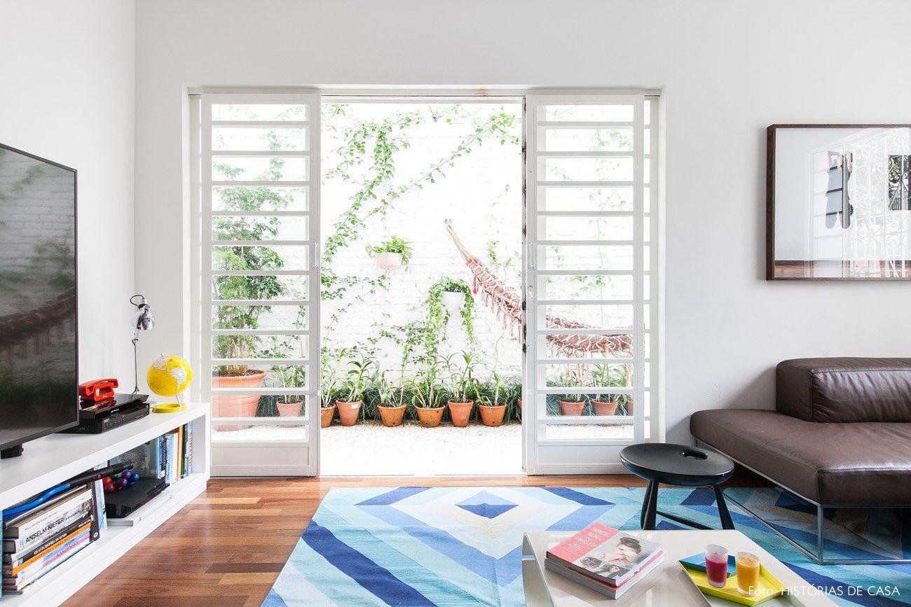 Sala de estar tem tapete com estampas geométricas, sofá de couro e banco assinado por Sérgio Rodrigues.