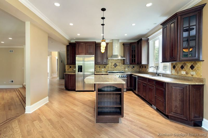 dark cherry cabinets, maple hardwood, and light countertops