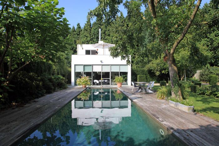 Delightful At The Edge Of The Woods Stands A Small White House. A Beautiful Home With