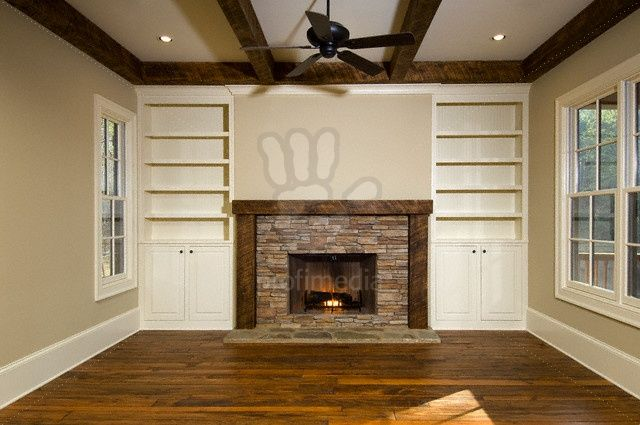 Empty Living Room With Brick Fireplace And Built In Shelves