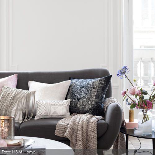 Dekokissen in Rosa, Grau und Weiß zieren das graue Sofa im