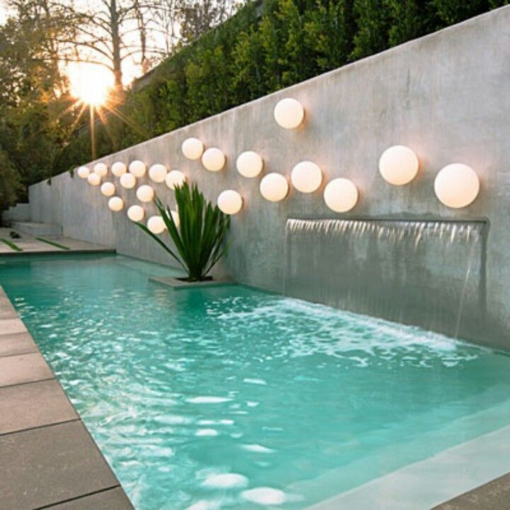ignore the globe fest streamlined waterfall into pool Piscina