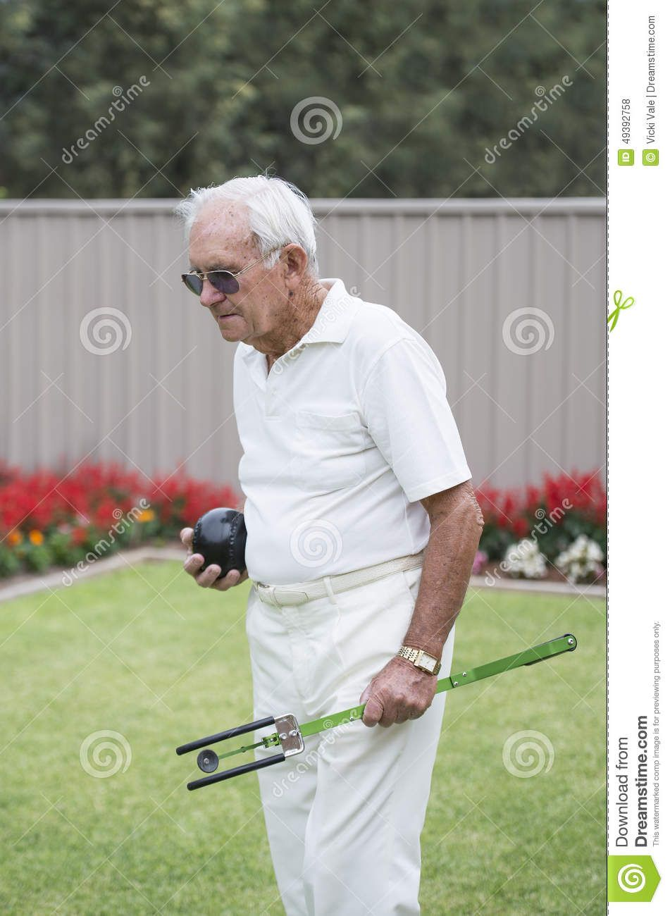 An elderly male bowler carrying a bowling ball and artificial bowling arm.