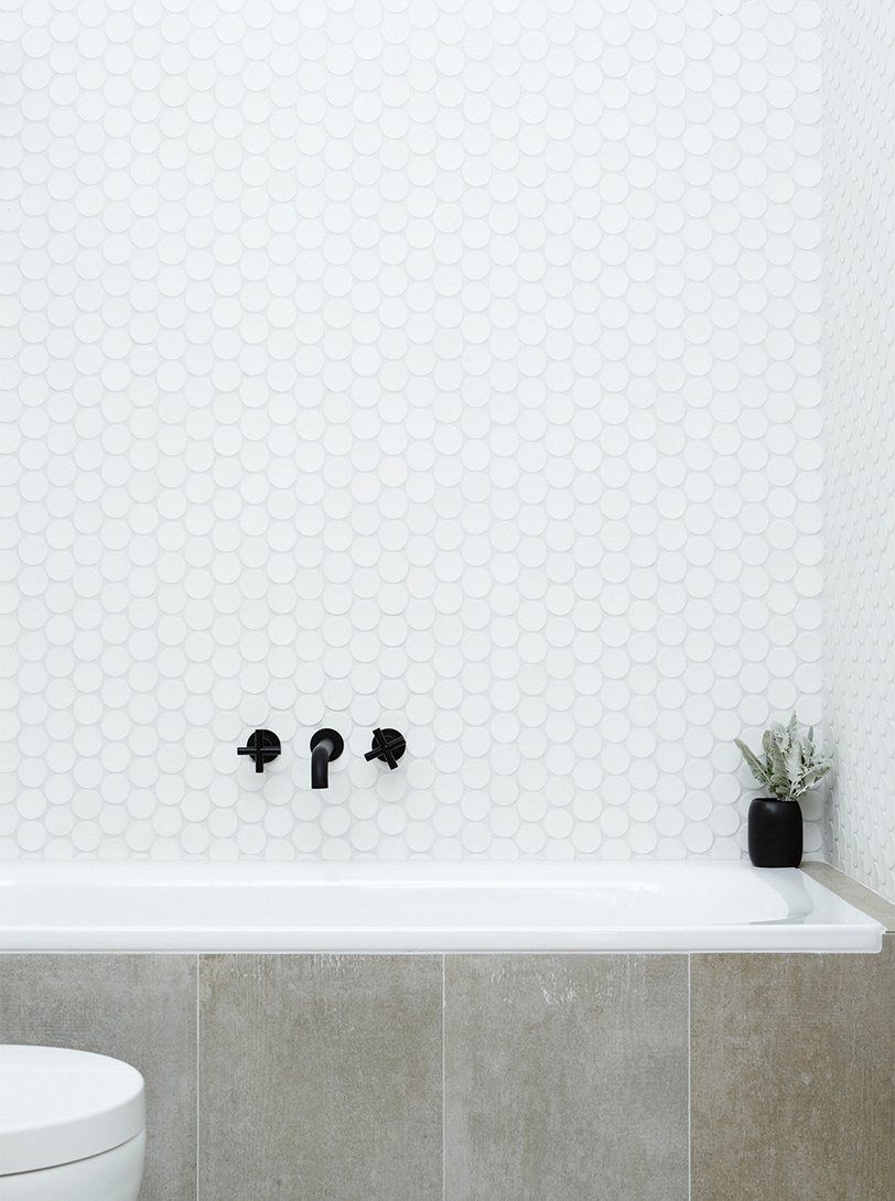 Bathroom with concrete bathtub siding, circular mosaic tile wall ...