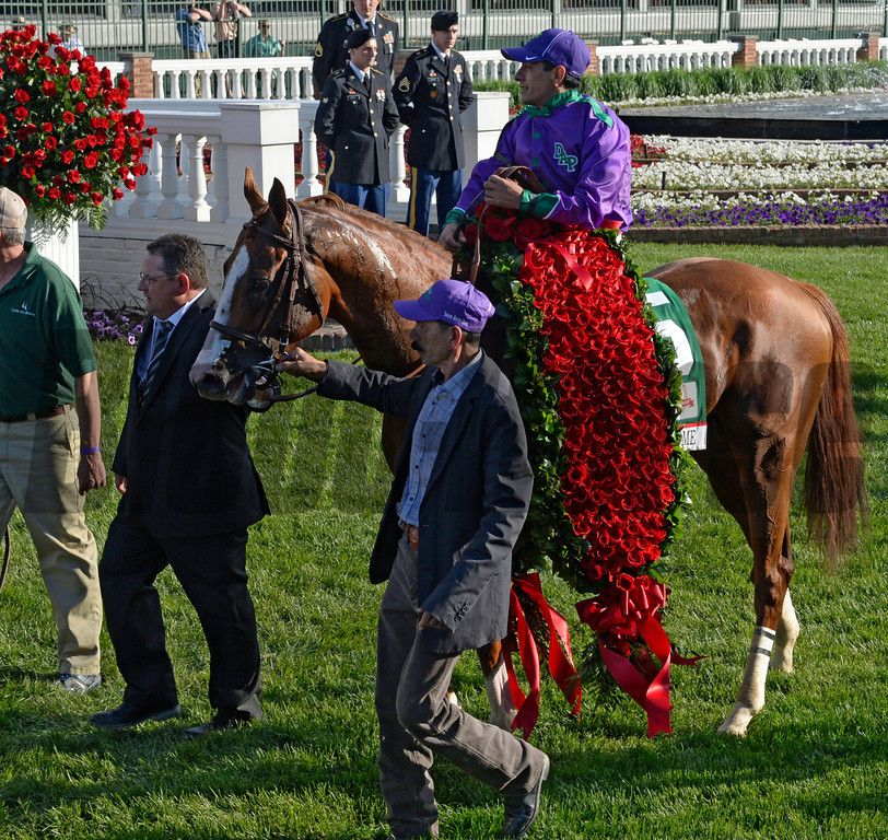 Victor Espinoza rides in to the winner's circle with the blanket of roses after winning the 140th running of The Kentucky Derby aboard California Chrome. Skip Dickstein Photo