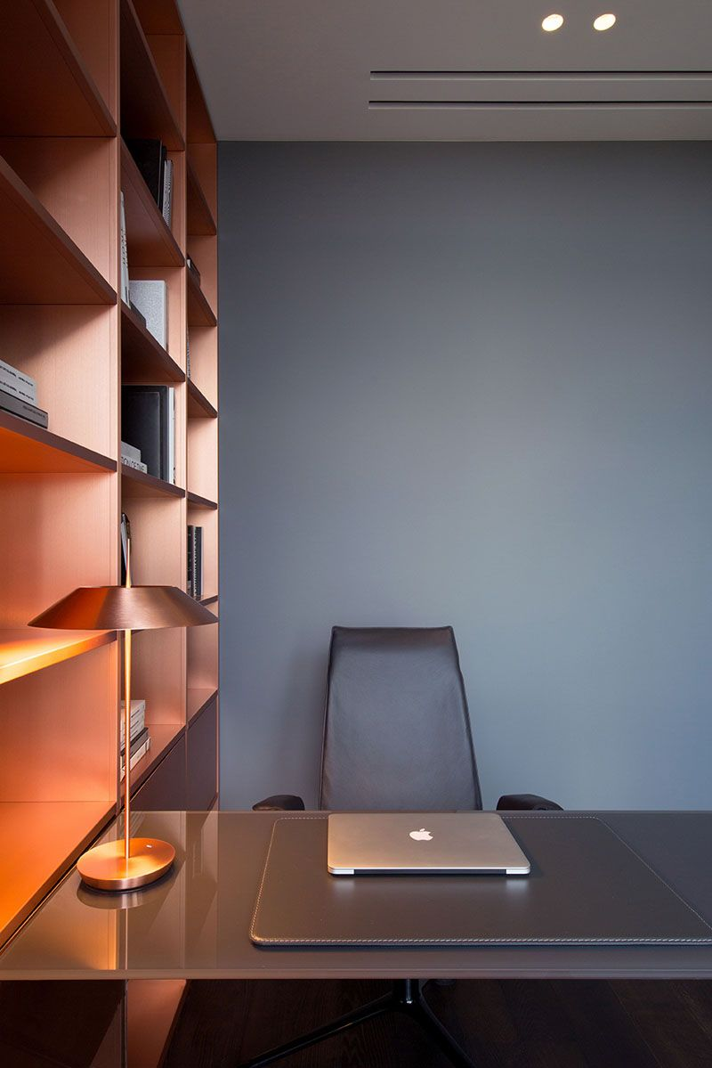 in this modern home office copper shelving adds a metallic touch to the grey walls
