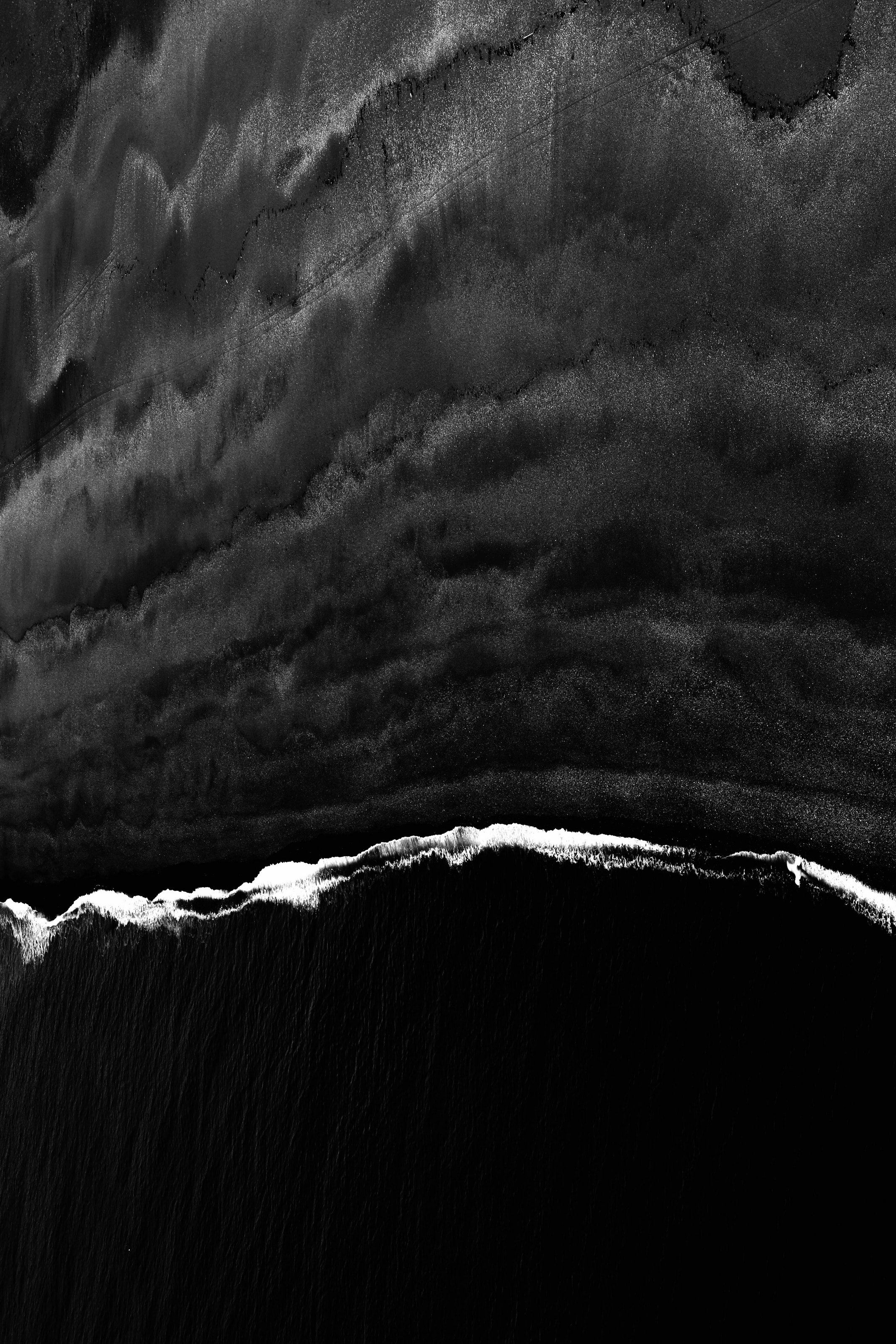 Black And White Drone Shot Of Shoreline With Tide Waves Coming In
