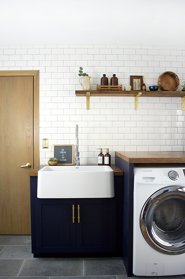 Laundry Room With Farmhouse Sink Navy Cabinets And Subway Tile