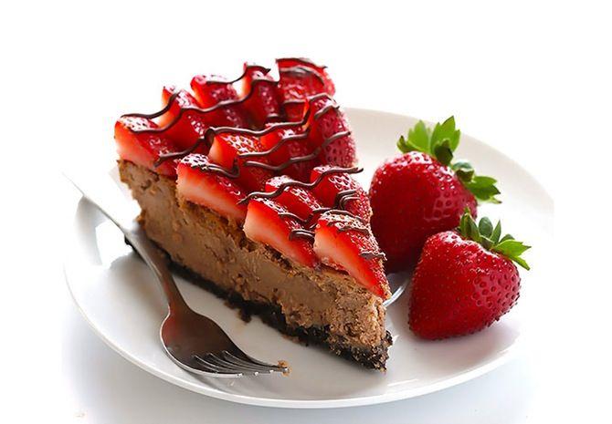 Et stykke cheesecake med jordbær på toppen og jordbær on the side.