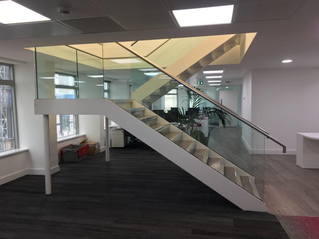 White steel staircase with frameless glass balustrade