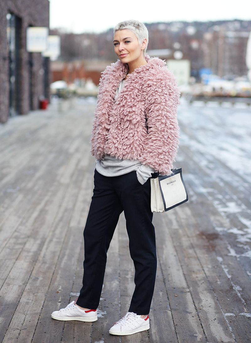 Marie Ullevoldsater is wearing a pink H&M fur coat, black Mq pants and Stan Smith Adidas sneakers. I love this look