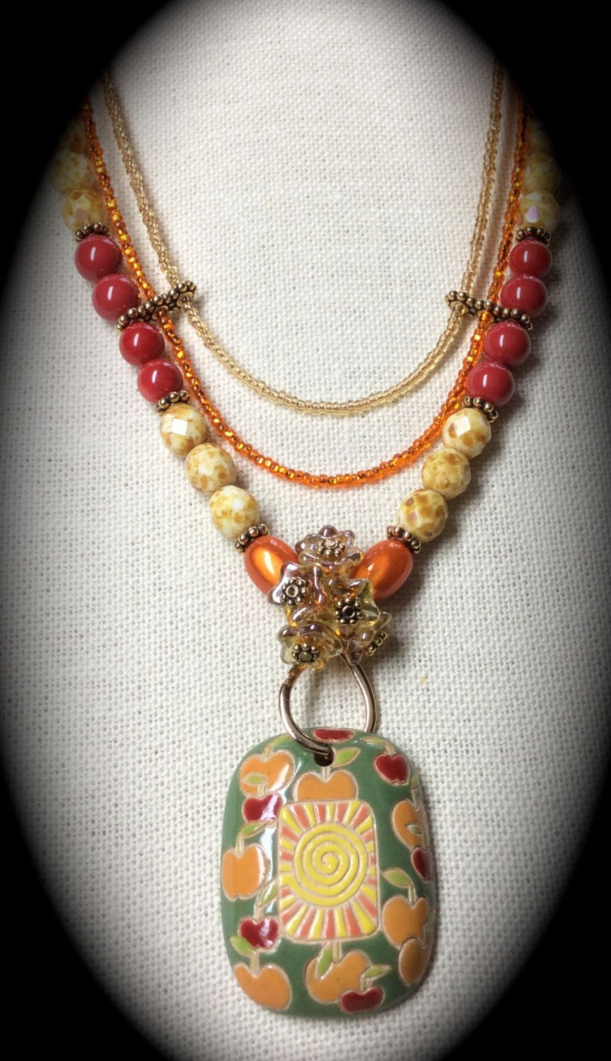 "Red coral crystal pearls, Picasso beads, glass flowers and Orange ""Miracle Beads all come together with bright seed bead strands to grab the apples and oranges on this hand-painted porcelain pendant, done exclusively by Russian artist, Golem. Perfect for a cool Autumn day, with the smell of wood-burning fireplaces in the air, leaves falling, and you wearing a warm turtle neck sweater, highlighting this beautiful Finales creation... a one-of-a-kind!"