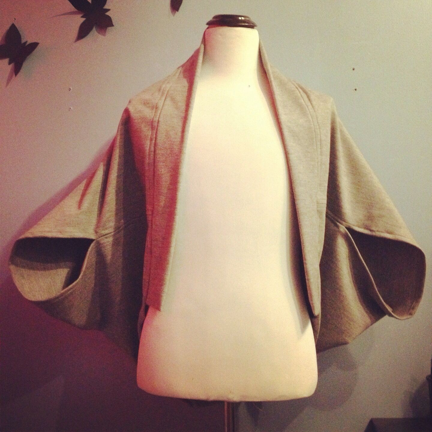 Grey wool cape with oversized sleeves.