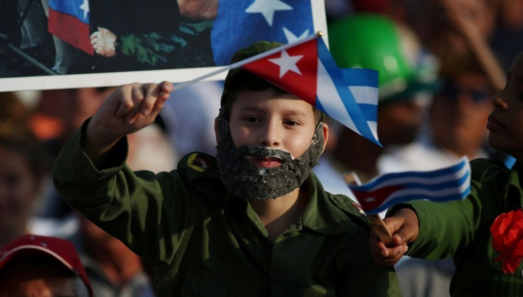 In Show of Continuity, Castro Flanks New Cuban Leader at May Day Rally -  At Cuba's first major political rally since Raul Castro handed the presidency over to his protege Miguel Diaz-Canel, the two men stood side-by-side overseeing Havana's May Day march on Tuesday in a show of continuity and unity on the Communist-run island      A boy wears a fake beard during the May Day rally in Havana #cubanleader In Show of Continuity, Castro Flanks New Cuban Leader at May Day Rally -  At Cuba's fir #cubanleader