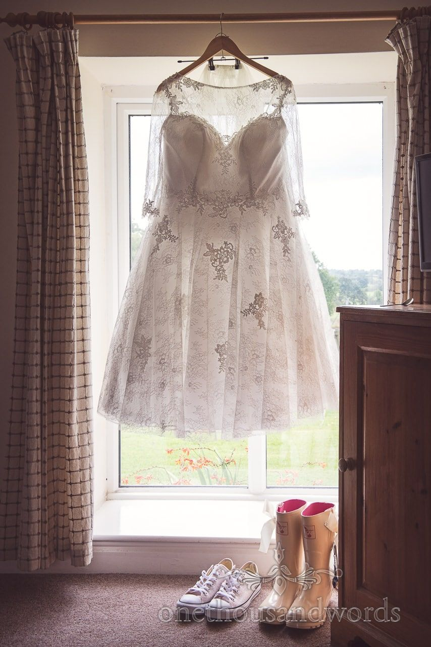 a5c54951be0 Tea length wedding dress with lace detail hangs in window at Coppleridge  Inn Wedding. Photography