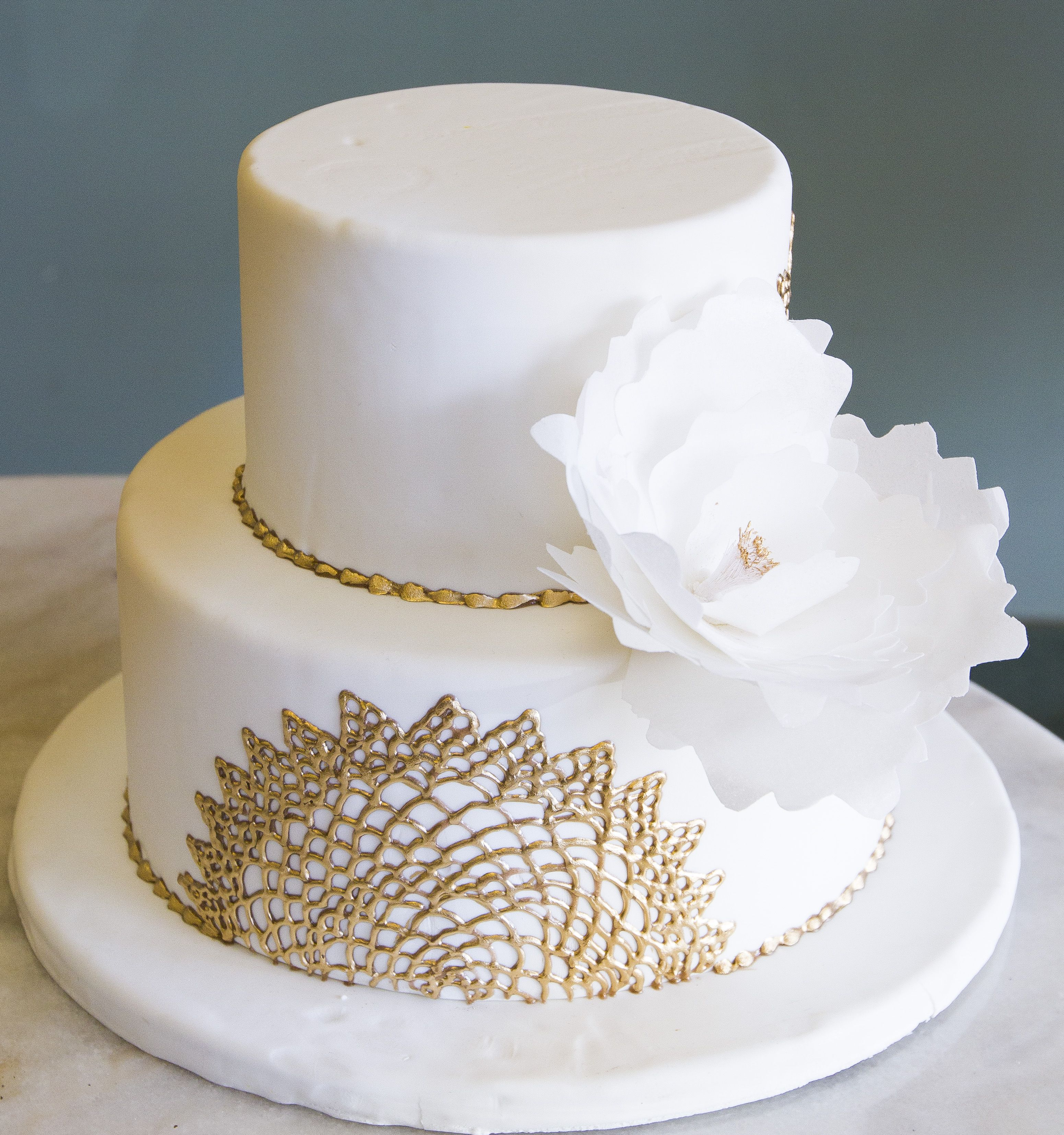 A simple white wedding cake with touches of gold! Cake