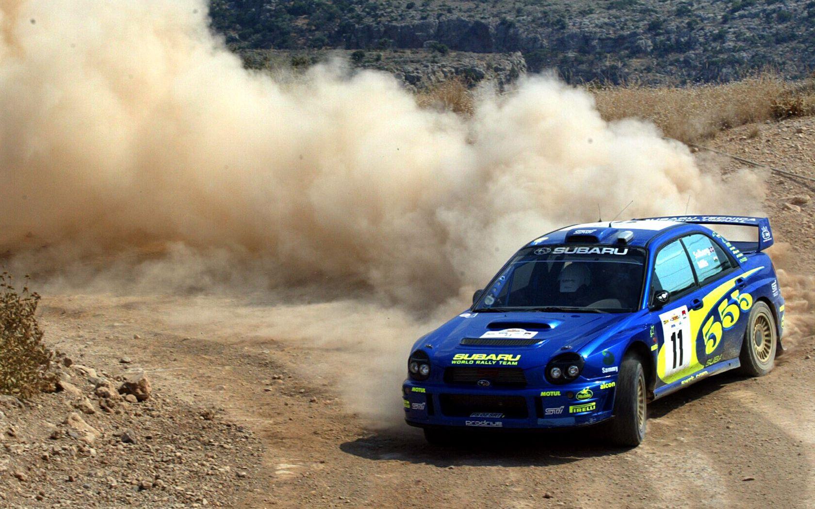 Rally car blue subaru drifting leaving a massive dust cloud in its wake