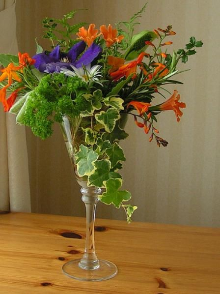Flower arrange in wine glass wedding centerpieces on a