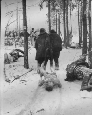 Soviet POWs collect their countrymen's bodies after a fight. Finnish soldiers in background.