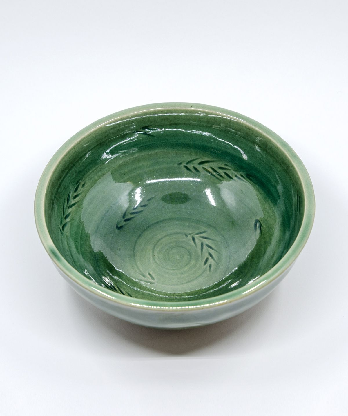 The medium cermic bowl is carved with a spiral floral motif, glazed outside and inside with a green shiny transparent glaze, a stone ware bottom. Pottery handmade art by #gosha_ceramics // #pottery  #fruitbowl #poterie #clay #claylove #handmade #handmadeceramics #ceramics #ceramiclove #céramique #pottersofinstagram #ilovepottery #bowl #tableware #wheelthrown #wheelthrowing #ceramicart #funcionalpottery