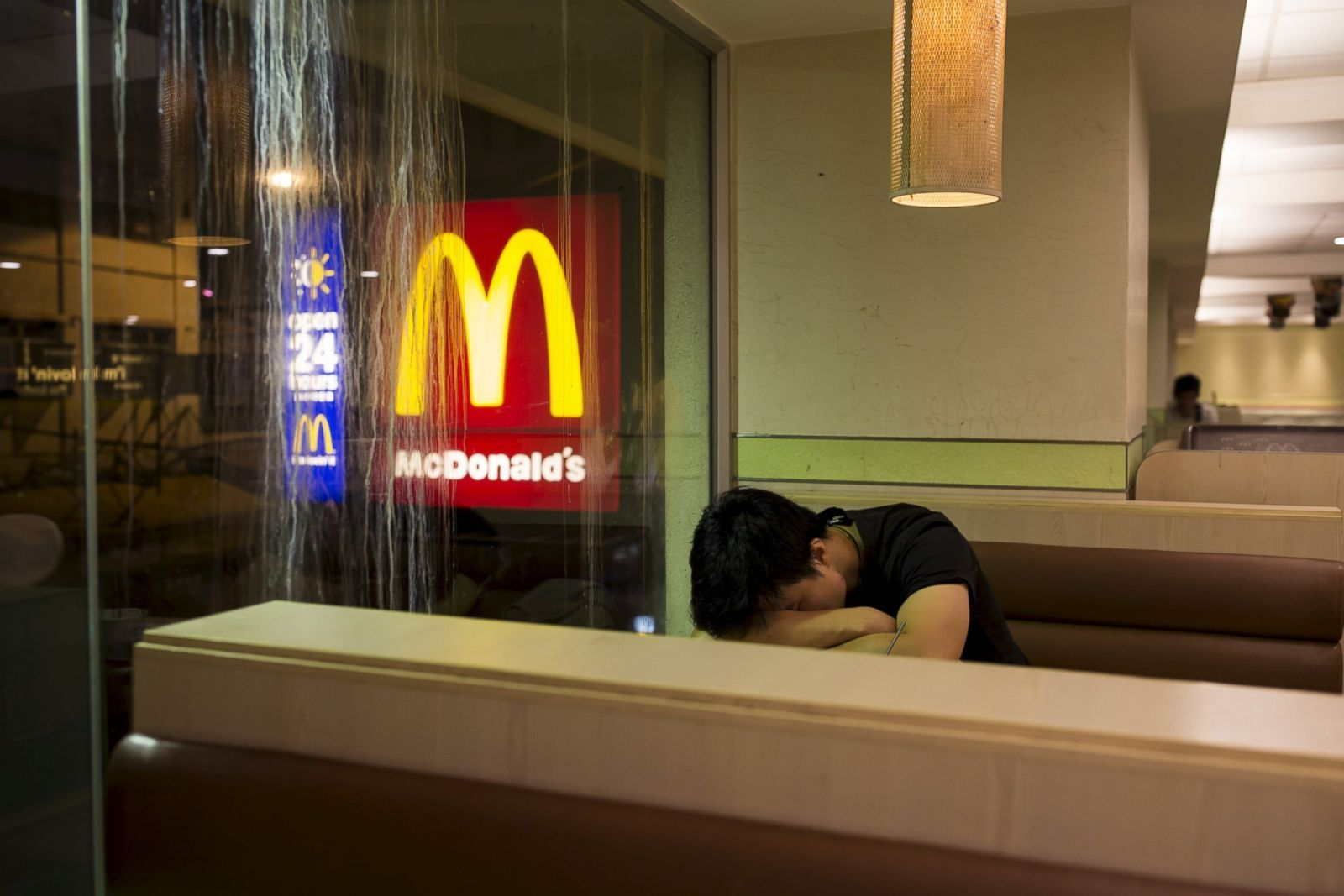 """Homelessness has long been a problem in Hong Kong due to high rents and soaring property prices. In recent years, the opening of McDonald's 24-hour fast food restaurants all over the city has presented an alternative for homeless people known as """"McRefugees"""" or """"McSleepers"""" to spend the night in a safer and more comfortable environment than the street. Pictured: A man sleeps at a 24-hour McDonald's restaurant in Hong Kong, China, Nov. 10, 2015."""